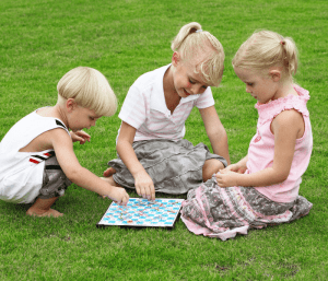 Children playing a game outside. This post is all about how to hire a nanny for twins.