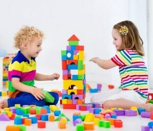 Twins playing with blocks. This post discusses the best toys for twin toddlers.