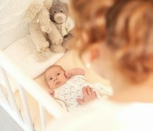 Mom putting baby in crib awake. Find out when to start putting baby down awake.