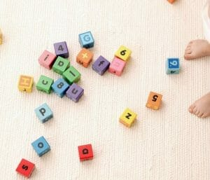 Toy blocks spread out on the floor. This section is all about toddler parenting.