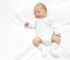 Baby sleeping on white sheets. This section is all about helping parents with their baby's sleep.