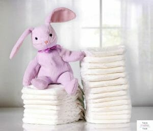 Diapers stacked in front of window with a stuffed bunny on top. This post discusses diaper blowout hacks and prevention.