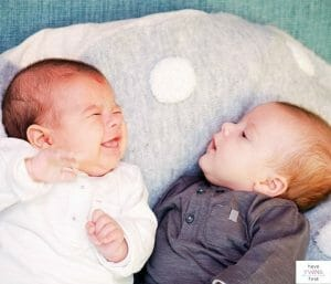 Twin babies lounging on a pillow. This post is all about the best twin feeding pillows.