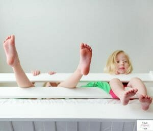 Two kids hanging out in bed. This article discusses tips for transitioning twins to toddler beds.