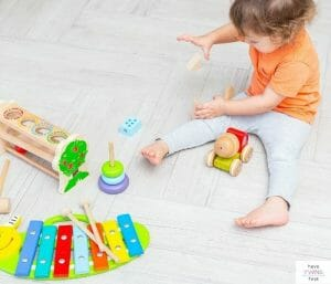 Toddler playing with toys on floor. This article discusses the top toddler must haves.