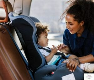 Mom putting baby in car seat. This article discusses the best narrow car seats on the market.