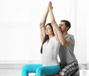 Pregnant mom and partner practicing labor breathing and relaxation. This article discusses if birthing classes are worth it.