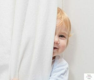 Baby hiding behind a curtain. This post covers the best blackout curtains available for the nursery.